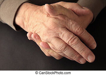 Older man holding his numb hand - An older man grasps his...