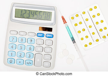 Calculator, syringe and pills on grey background - studio...