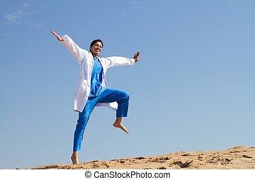 cheerful nurse jumping on beach in scrubs