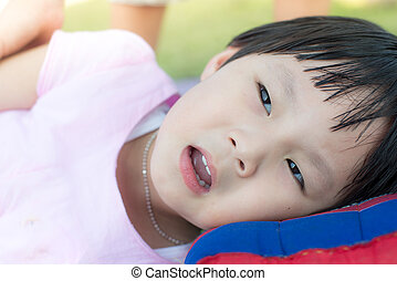 Happy Asian girl laying with pillow outdoor.