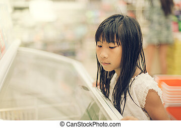 Asian girl in front of sweet candy food store window, colour...