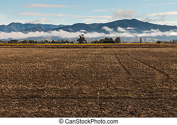 ploughed field - closeup of ploughed field with mountains in...