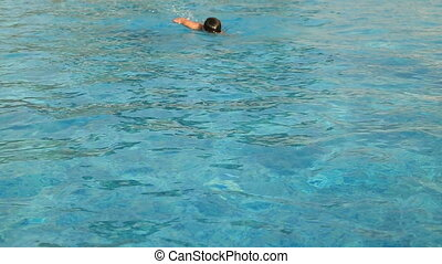 Little swimmer swimming - Young boy in goggles swimming...