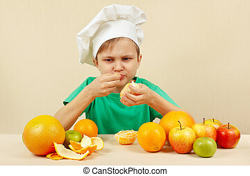 Little funny boy eat acidic orange at table with fruits -...