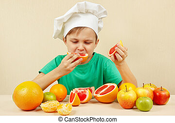 Little funny boy eat acidic grapefruit at table with fruits...