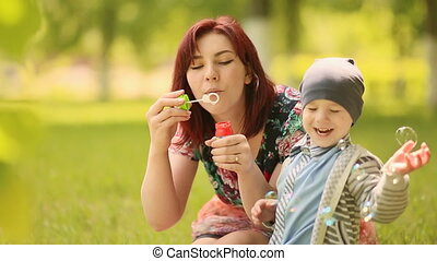 Young mother and baby blow bubbles