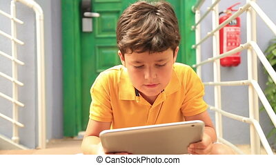 Young boy using digital tablet - Young boy sitting on a...