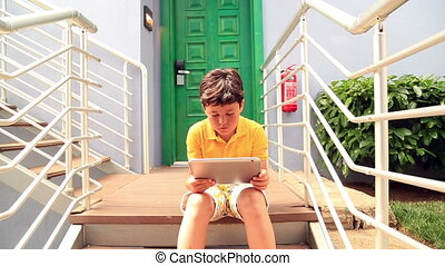 Young boy using digital tablet - Caucasian young boy sitting...