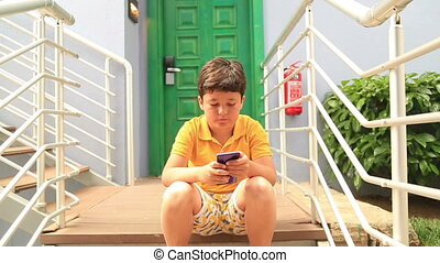 Young boy using smartphone and smiling to camera