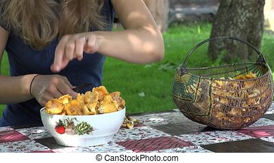 peasant girl clean chanterelle mushrooms on table. 4K -...