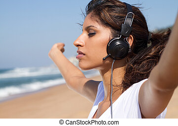 freedom woman on beach with earphones on and arms...