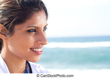 profile of young indian doctor on beach