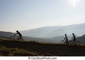 Three bikers on a mountain trail