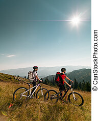 couple of mountain bikers - mountain bikers on a meadow,...