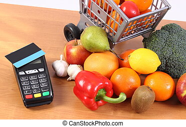 Payment terminal with contactless credit card, fruits and...