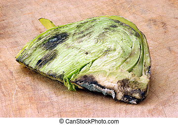 mouldy organic vegetable unhealthy to eat on a timber board