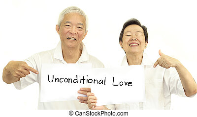 Happy Asian senior couple holding sign unconditional love