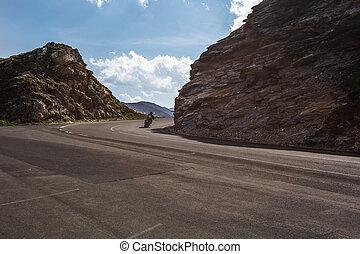 Biker passes on motorcycle on road between rocks in...