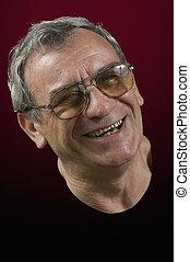 senior laughing man - matured laughing man against the dark...
