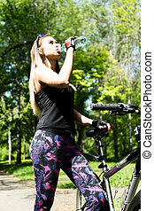 Portrait of pretty young woman with bicycle in a park - outdoor. she drinks water from a bottle