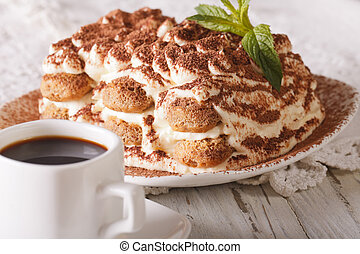 Italian Tiramisu cake on a plate and cup of black coffee close-up. Horizontal