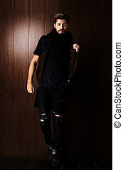 Handsome confident mature man with beard stands on wooden...
