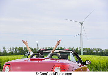 Woman in a red cabriolet in a field. - Woman in a red...