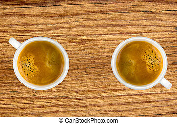 Two cups of coffee on wooden table, top view
