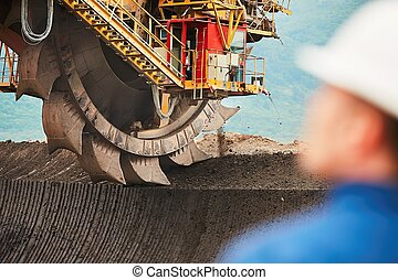 Coal mining in an open pit - Worker is looking on the huge...