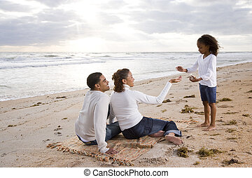 African-American girl with parents on beach - Six year old...