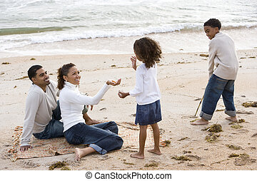 Happy African-American family playing on beach - Happy...