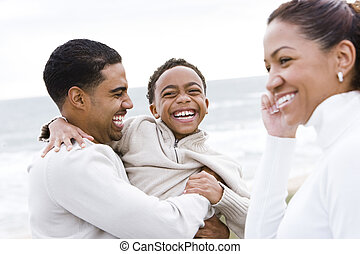 African-American boy with parents laughing on beach