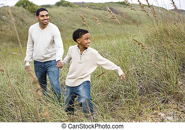 African-American boy walking with father along sand dunes -...