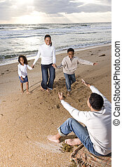 African-American family running to dad on beach - Happy...