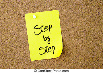 Step By Step written on yellow paper note pinned on cork...