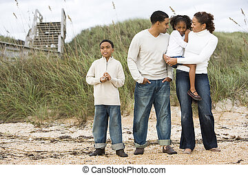 Happy African-American family standing together on beach -...
