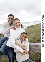 African-American family laughing and hugging at beach -...
