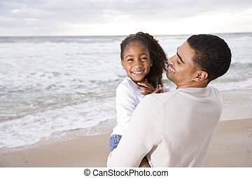 African-American dad hold little girl at beach - Happy...