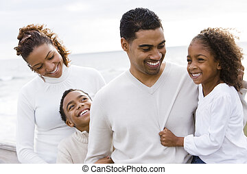 African-American father and two children on beach - Happy...