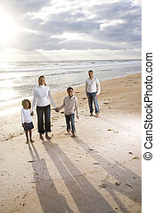 Happy African-American family of four standing on beach with...