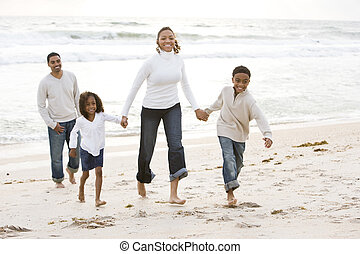 African-American family walking on beach - Happy...