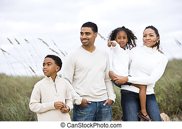 Happy African-American family standing together at beach -...
