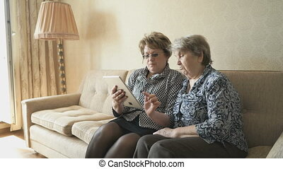 The old woman and her friend looking at pictures using a...