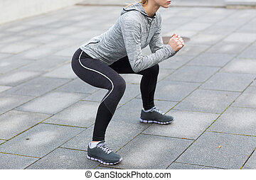 close up of woman doing squats outdoors - fitness, sport,...