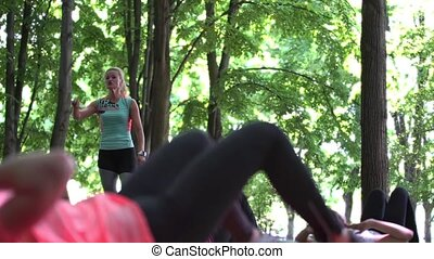 Fitness class with instructor doing exercise in park
