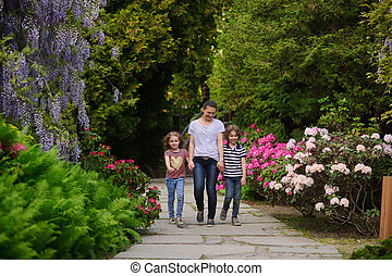 Mother with two children on a walk in the lush garden
