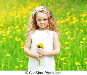 Beautiful little girl child on meadow with yellow dandelion flowers in sunny summer day