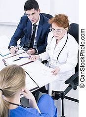 Doctor's meeting in office - Young male doctor and older...