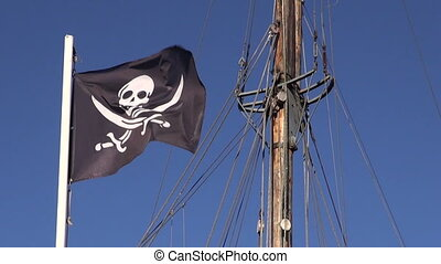 Sunlit pirate flag waving in wind - Black pirate flag waving...