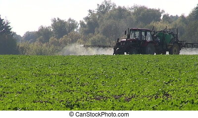 Tractor spraying crop field - Tractor spraying field with...
